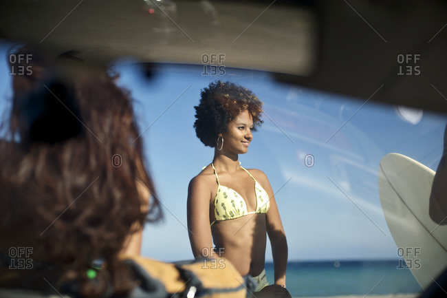 A woman stands in front of a car at the beach