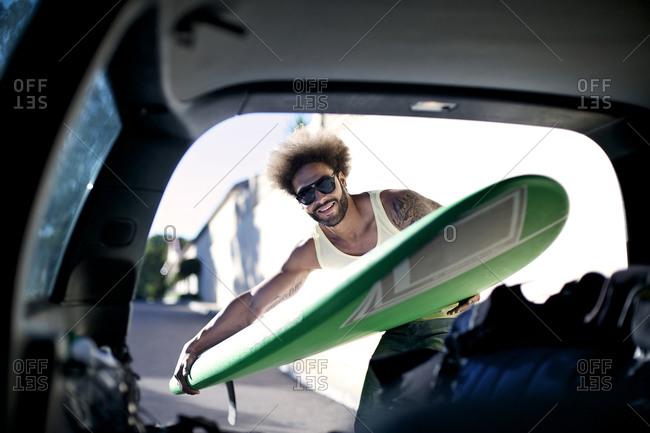 A surfer unloads a surfboard from a car