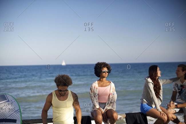 Two couples sit on a railing at the beach