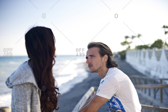 A couple talks on a pathway to the beach
