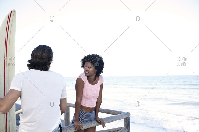 A couple stands on a pier