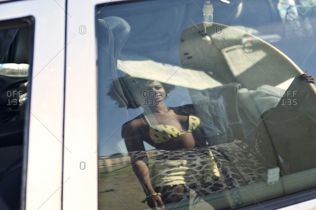 The reflection of a woman holding a surfboard