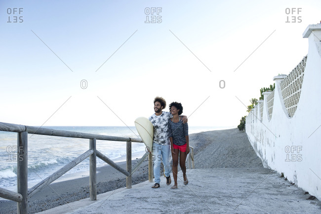 A couple walks up a ramp at the beach
