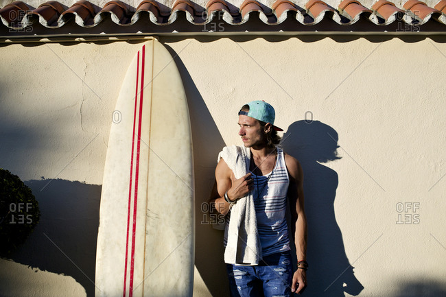 A surfer leans against a wall