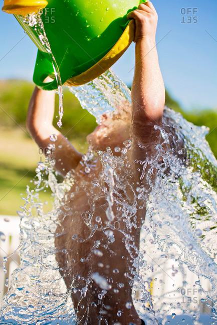 Little boy splashing himself with pail
