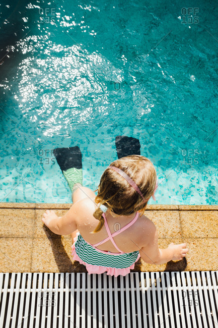 Girl sitting at edge of pool with flippers on