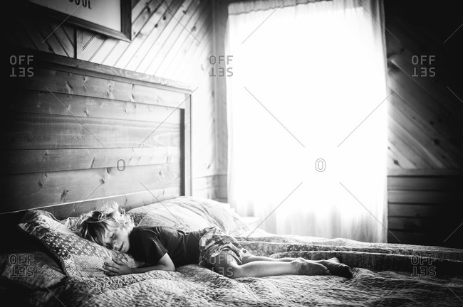 Young child napping in a bedroom with sunlight coming through window