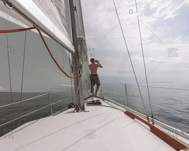 A man drinks a beer on the bow of a ship