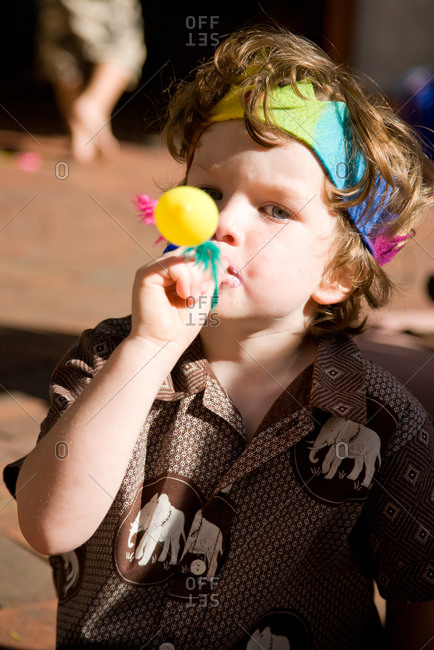 Boy blowing party favor at birthday party