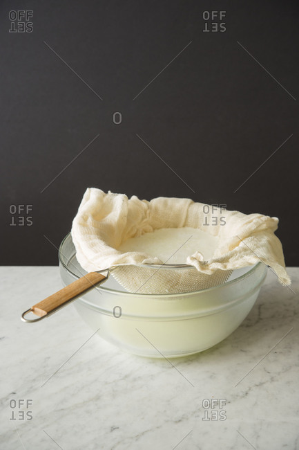 Cheese in cheesecloth and a sieve