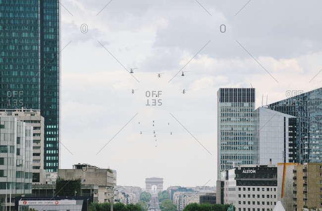 Paris, France - July 14, 2011: Squadron of 16 helicopters from the French Air Force Patrouille de France as they fly over the La Defense to the Champs-Elysees avenue during the annual Bastille Day military parade