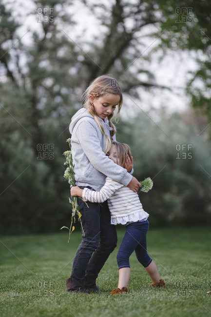 Little sister hugging her big sister