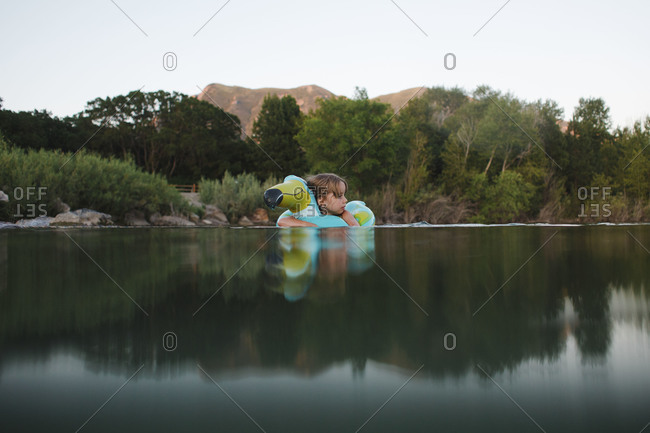 Little girl swimming with a float toy