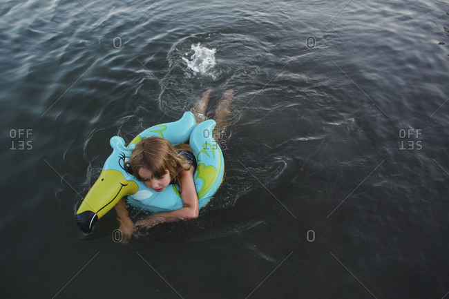 Young girl swimming with a float toy