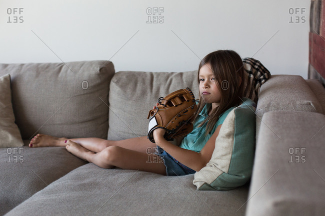 Girl sitting on couch wearing baseball mitt