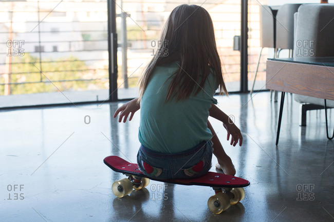Girl sitting on skateboard in living room