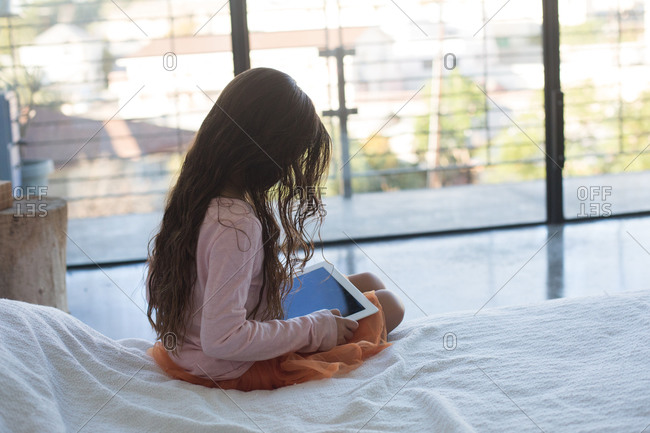 Girl sitting on a bed with tablet