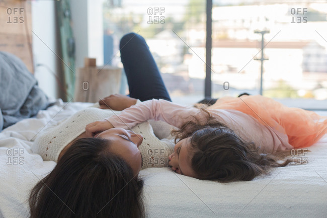 Girl and woman asleep side by side on bed