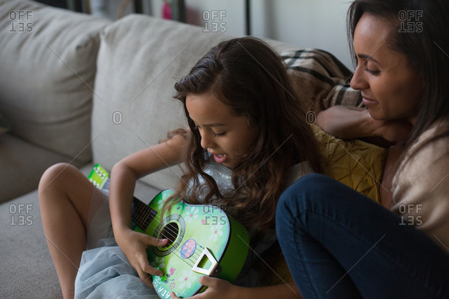 Girl strumming guitar sitting with mom