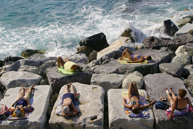 Italy, Liguria, Zoagli - June 29, 2004: People sunbathing on boulders in Italy