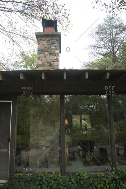 Kingwood Township, New Jersey - March 16, 2000: Glass windows and a stone chimney of James Golden's ranch home
