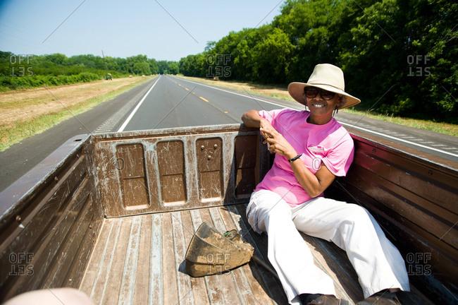 Colfax, Louisiana - May 28, 2012: Malva Kimble rides in the back of a pickup truck