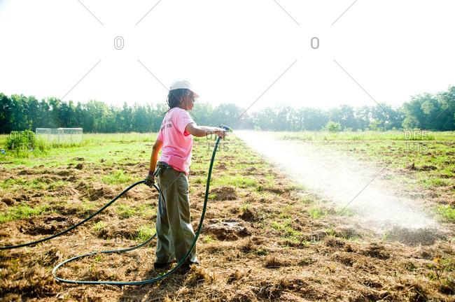 Colfax, Louisiana - May 28, 2012: Dianne Kimble waters her garden
