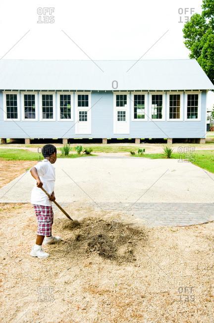 A boy breaking up soil for a garden in Louisiana