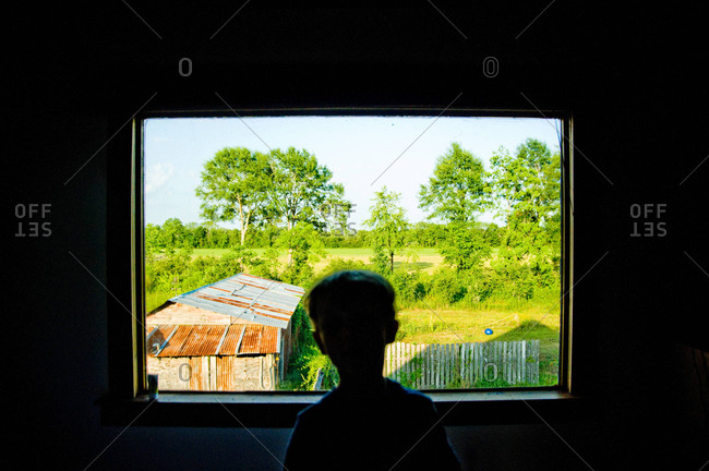A boy looks out of a window of a bousillage home