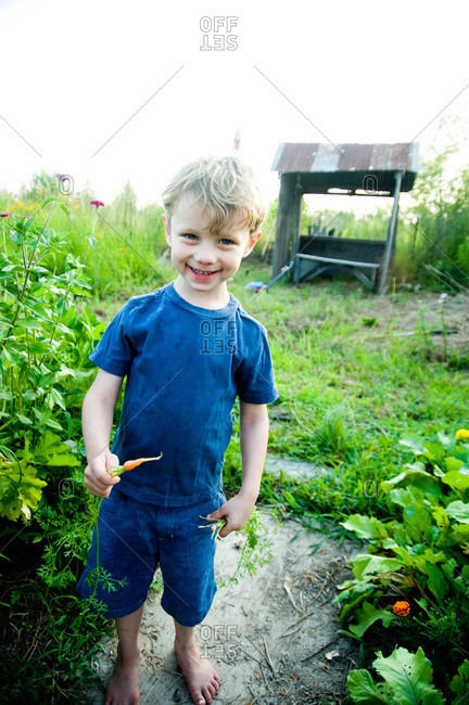 Arnaudville, Louisiana - May 29, 2012: Julien Michot holds a baby carrot in his family's garden
