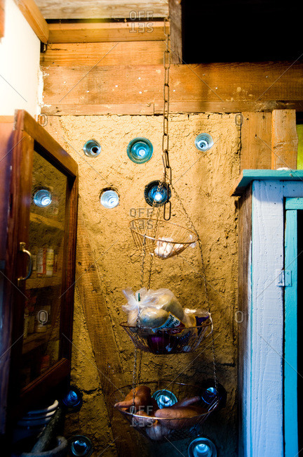 Mud and Spanish moss walls with portholes made from old electrical insulators in a bousillage home