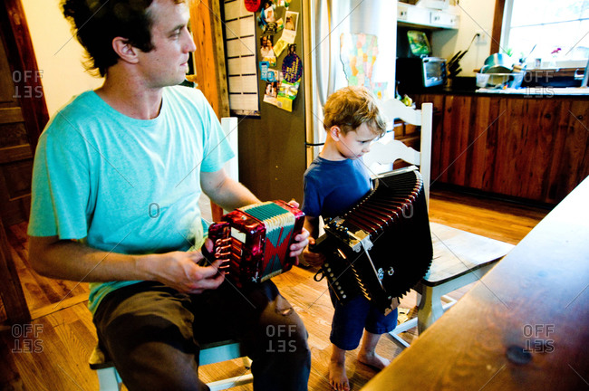 Arnaudville, Louisiana - May 29, 2012: Louis Michot, of the Lost Bayou Ramblers, and son playing accordions together in a bousillage home