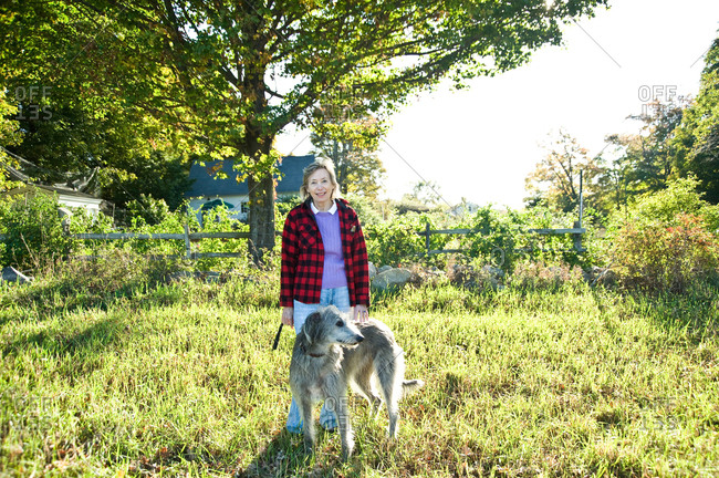 North Salem, New York - October 9, 2010: Page Dickey and her dog on an overgrown lawn