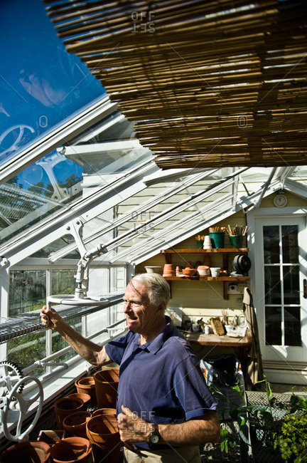 North Salem, New York - October 9, 2010: Bosco Schell, Page Dickey's husband, turns a crank to open windows in his greenhouse