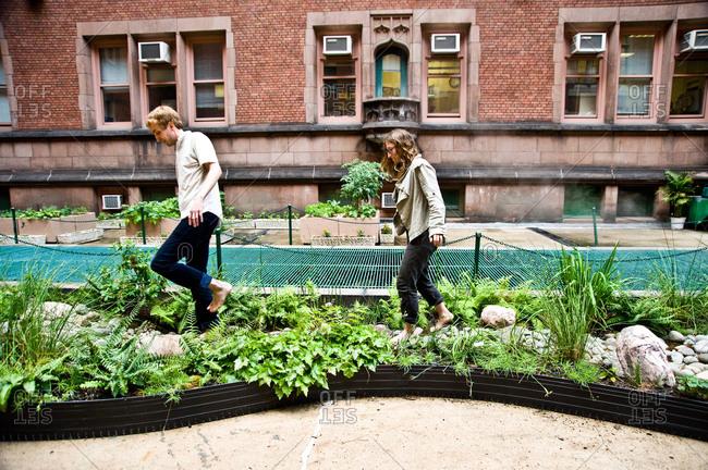 New York City, New York - June 14, 2011: Colin Schumacher and Marni Majorelle walk barefoot through a rain garden