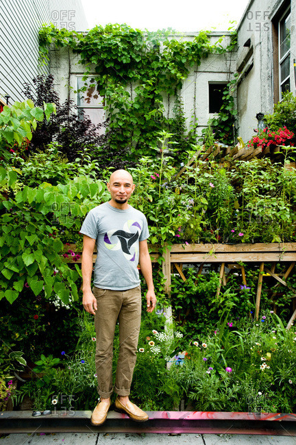 Brooklyn, New York - June 19, 2012: Alex Aguilar stands next to his rooftop garden