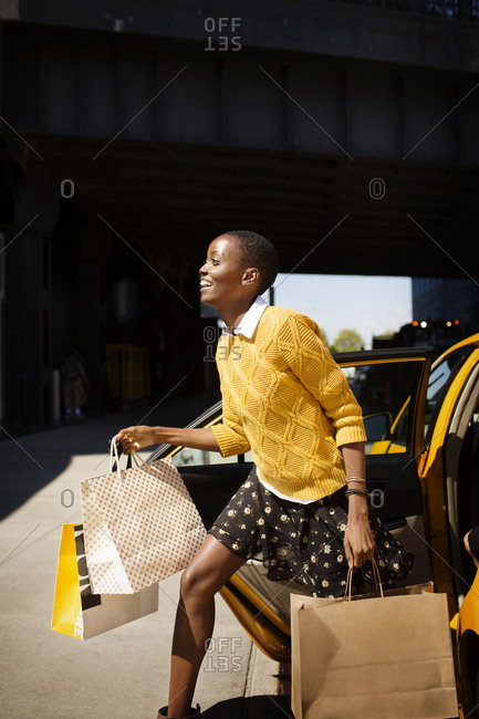Woman exiting cab with shopping bags