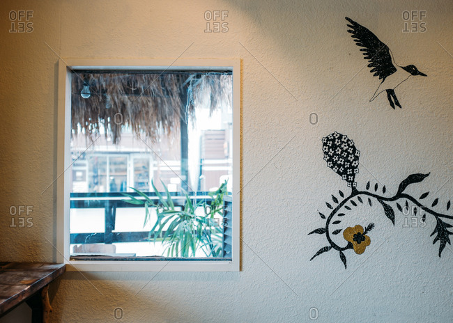 Tropical painting on wall by window