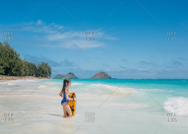 Girl standing in ocean with body board