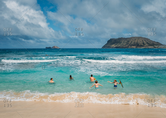 Family playing in ocean in Hawaii