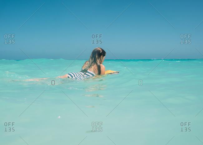 Girl floating on body board off Hawaiian coast