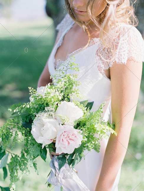 Bride holding white flowers outdoors