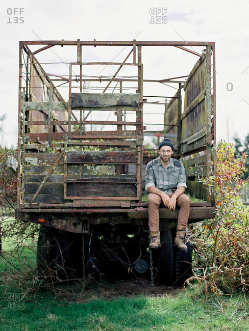 Man sitting on back of farm wagon
