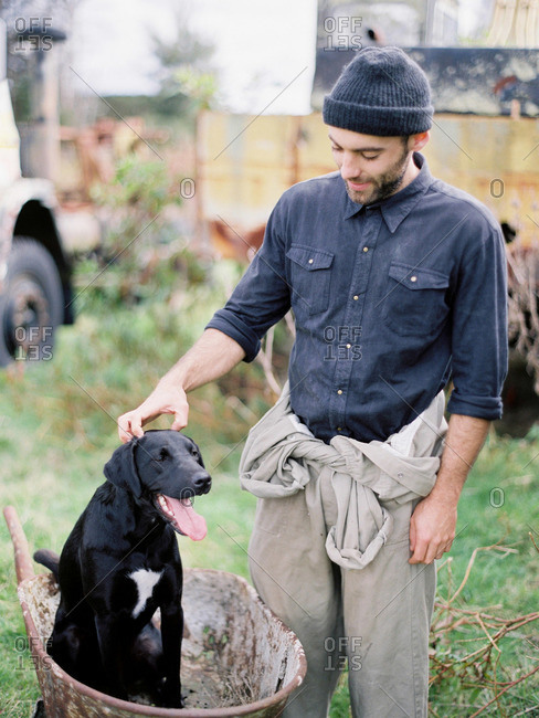 Man petting dog in wheelbarrow