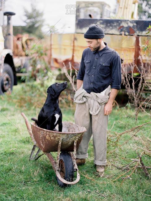 Man with dog in wheelbarrow
