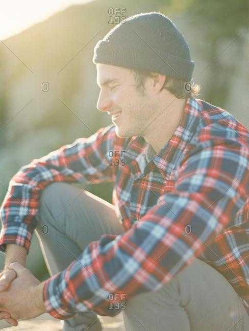 Man sitting in sun dappled outdoors