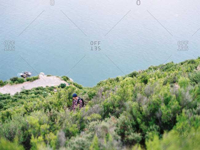 Man hiking on hill overlooking lake