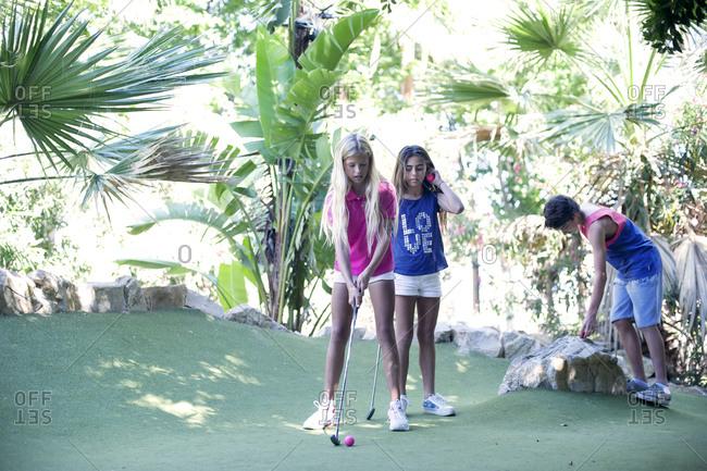 Three kids playing minigolf - Offset