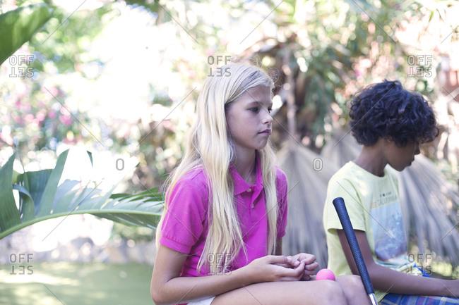 Boy and girl sitting while playing minigolf