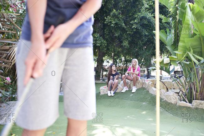 Teens playing minigolf